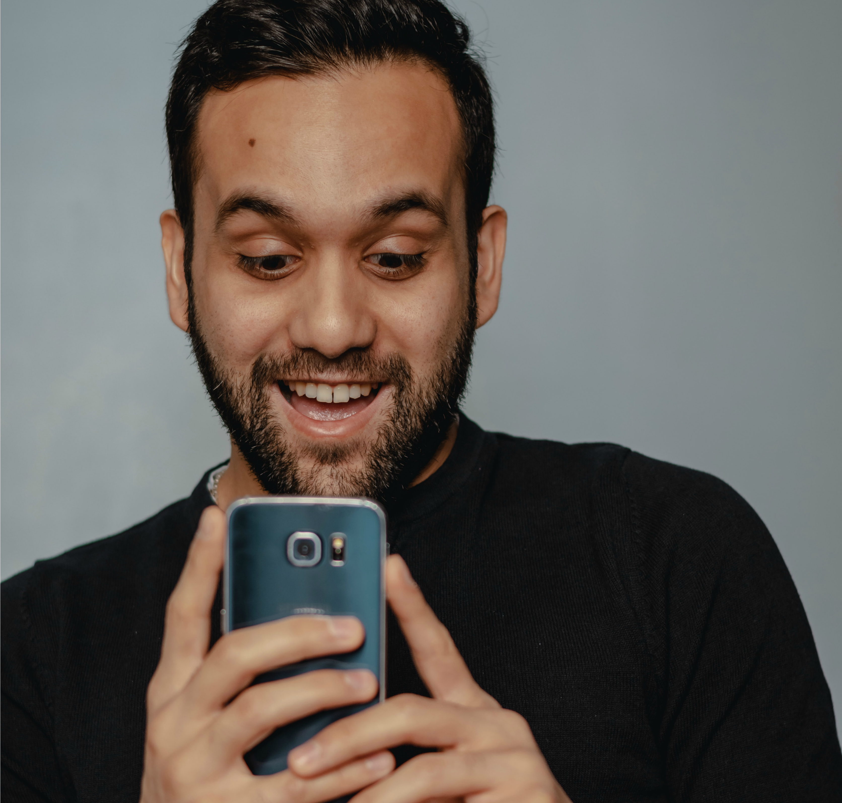 Man Looking at His Phone and is Thrilled