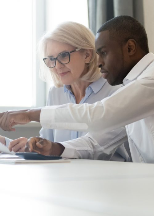 African american employee pointing at laptop discussing paperwork with colleague working together focused on computer task, black business employee helping giving online presentation to client